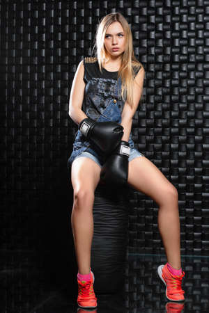 Nice young blonde posing sitting on a punching bag in boxing gloves Stock Photo