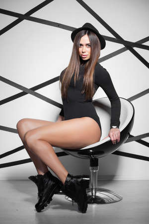 Charming woman sits on a chair in the studio, dressed in a black bodysuit and hat