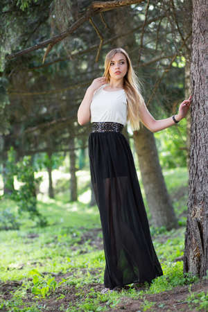 Alluring blonde woman posing among the firs in the street wearing a long dress Stock Photo
