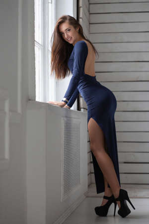 Nice woman posing standing near the window on the background of a wooden wall dressed in a long blue dress Stock Photo