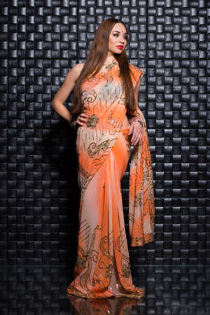 Alluring young woman wearing indian orange traditional sari
