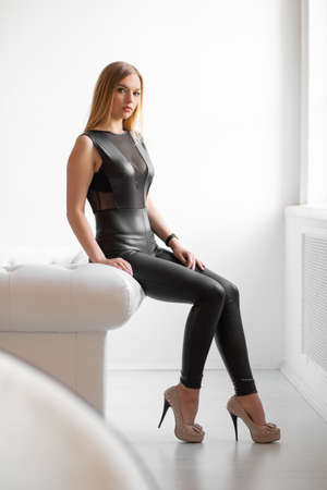 Cute young blonde posing in the studio dressed in a black leather suit