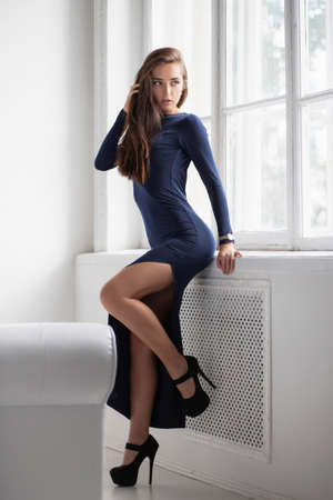 Nice brunette posing standing in a studio near the window, dressed in a long blue dress with a slit Stock Photo