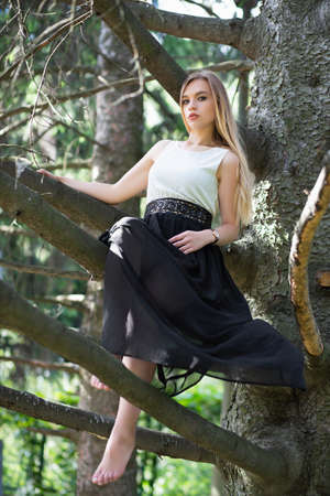 Nice young woman posing on a tree dressed in a long dress