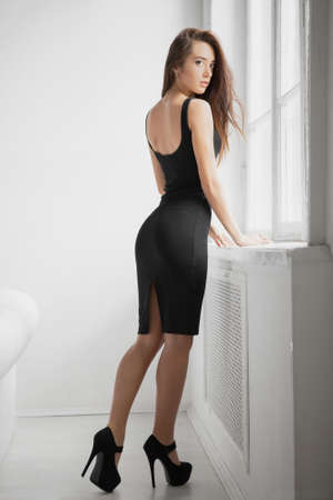 Beautiful young woman dressed in a black dress posing in a studio near the window