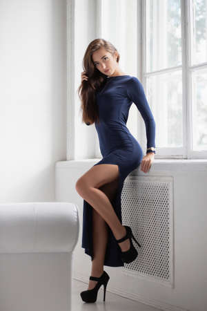 Attractive brunette posing standing in a studio near the window, dressed in a long blue dress with a slit Stock Photo