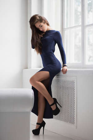 Pretty brunette posing standing in a studio near the window, dressed in a long blue dress with a slit