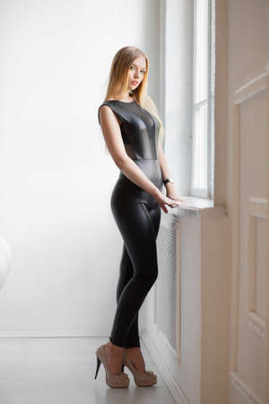 Adorable young lady posing in the studio dressed in a black leather suit