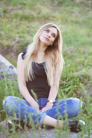 Young alluring woman posing sitting on a stone in the street wearing a t-shirt and jeans Stock Photo