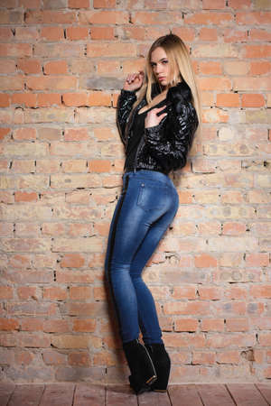 Pretty young lady posing on near the wall, wearing a black jacket and jeans Stock Photo