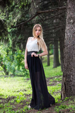Adorable blonde woman posing among the firs in the street wearing a long dress