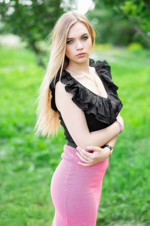 Young pretty blonde posing on a background of green grass, wearing a black blouse and pink skirt
