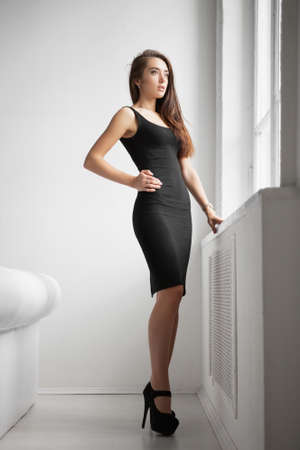 Pretty young woman dressed in a black dress posing in a studio near the window Stock Photo