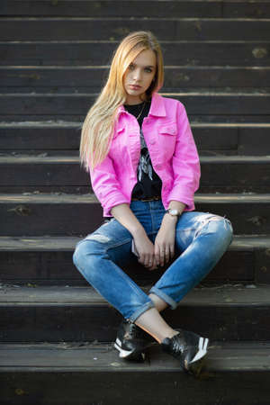 Alluring blonde posing outdoors sitting on the stairs dressed in a pink jacket and pants