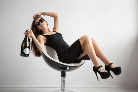 Smiling brunette in glasses posing sitting on a chair in the studio dressed in a black dress and holding a bottle in her hand