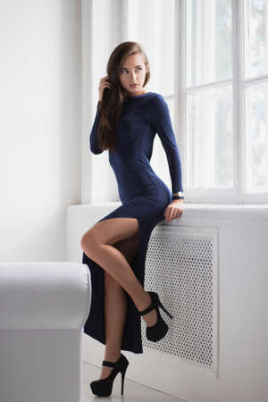 Young pretty brunette posing standing in a studio near the window, dressed in a long blue dress with a slit