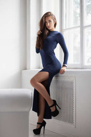 Beautiful brunette posing in a studio near the window, dressed in a long blue dress with a slit Stock Photo