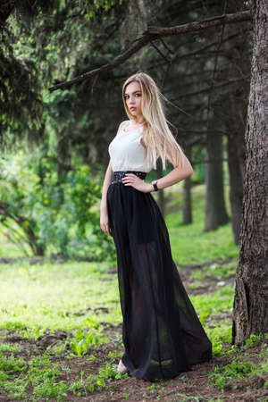 Cute blonde woman posing among the firs in the street wearing a long dress