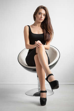 Pretty young lady posing sitting on a chair dressed in a black dress and shoes.
