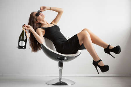 Charming brunette in glasses posing sitting on a chair in the studio dressed in a black dress and holding a bottle in her hand Stock Photo