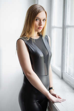 Portrait of a nice young woman posing in a studio, dressed in a black leather suit Stock Photo