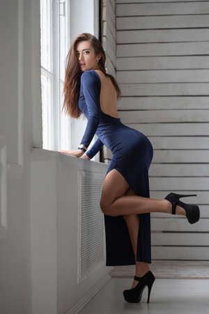 Beautiful woman posing standing near the window on the background of a wooden wall dressed in a long blue dress