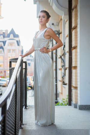 Charming young woman posing on the street near the handrail dressed in a long dress