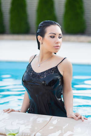 Beautiful lady posing in the summer in a pool dressed in a black dress