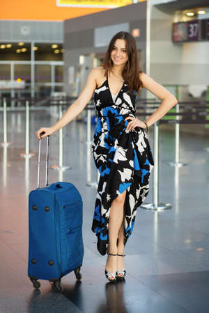 Young pretty brunette posing at the airport standing next to a suitcase dressed in a long dress 版權商用圖片