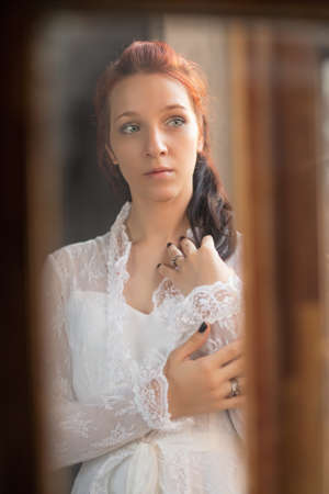 Portrait of a young elegance redhaired lady through a glass posing in the studio, wearing a white dress