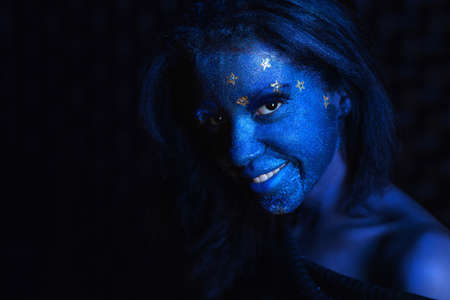 Young cute girl with blue face painting posing in studio on black background