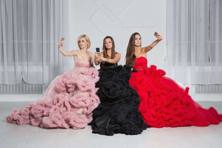Three nice girlfriends posing in the studio in luxurious evening dresses
