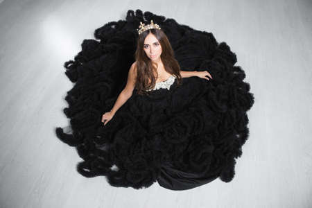 Adorable young woman poses in a studio dressed in a black puffy evening dress and crown