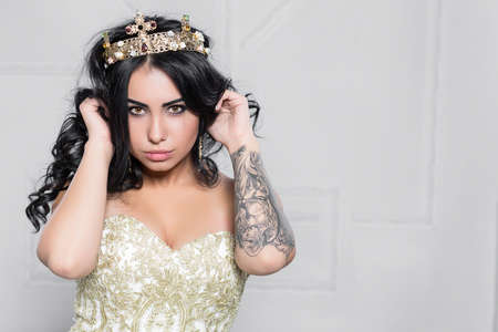 Portrait of a cute brunette with a tattoo on her arm posing in the studio dressed in an evening dress Stock Photo