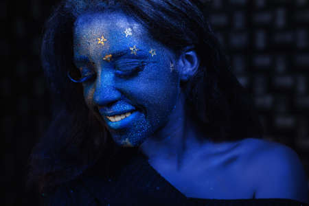 Young beautiful girl with blue face painting posing in studio on black background