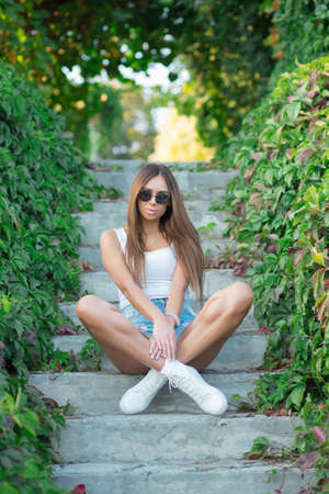 Young lovely brunette posing outdoors sitting on the stairs wearing a tank top and shorts