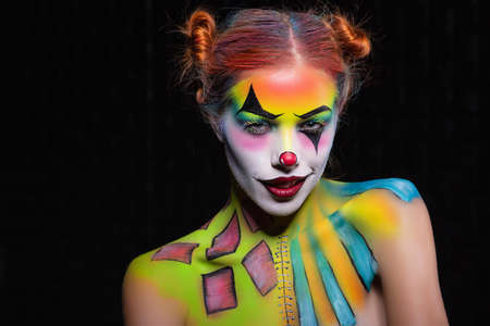 Playful lady with a face painting clown posing in the studio on a black background