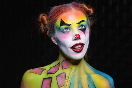 Cute young woman with a face painting clown posing in the studio on a black background Stock Photo