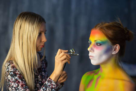 The artist puts a face painting on a beautiful young model in the studio, against a gray wall