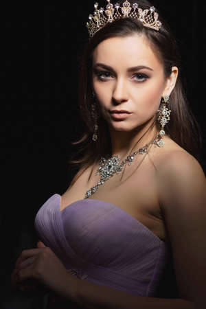 Sexy brunette posing in the studio on a black background dressed in an evening dress and jewelery. Stock Photo