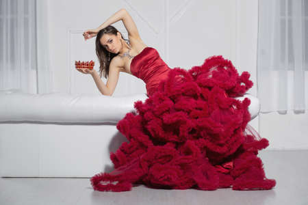 Sexy lady posing in a studio posing on a sofa dressed in a gorgeous red dress and a crown