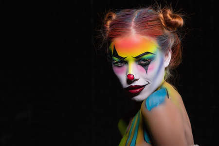 Charming young woman with a face painting clown posing in the studio on a black background