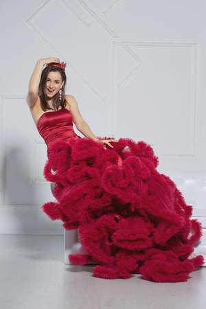Adorable young woman in a studio posing on a sofa dressed in a gorgeous red dress and a crown Stock Photo