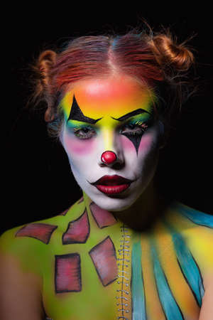 Attractive woman with a body art clown posing in the studio on a black background