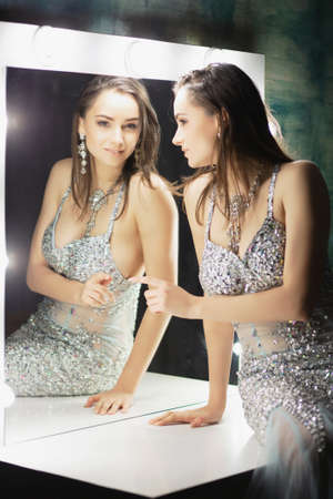 Adorable young brunette posing in a studio sitting on a table looking into mirrors dressed in an elegant blue silver dress with stones. Stock Photo