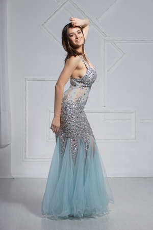 Gorgeous young brunette poses in a studio dressed in an elegant blue silver dress with stones