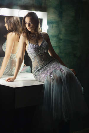 Alluring brunette posing in a studio sitting on a table near a mirror dressed in an elegant blue-silver dress with stones