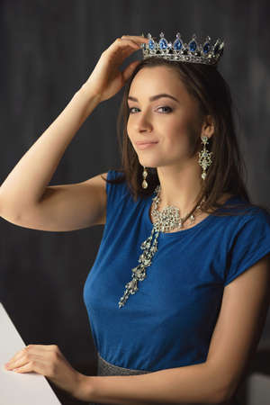 Portrait of a cute young brunette posing in a studio near the table dressed in a blue dress and a crown