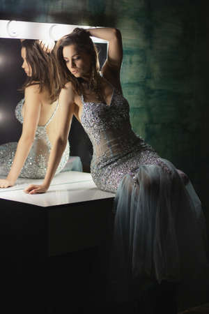 Pretty brunette posing in a studio sitting on a table near a mirror dressed in an elegant blue-silver dress with stones