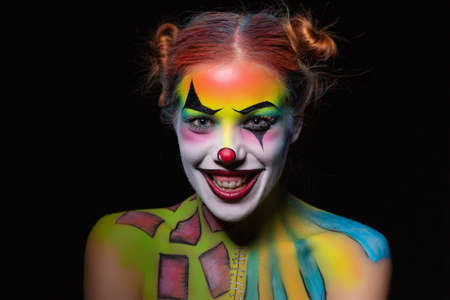 Cheeful woman with a body art clown posing in the studio on a black background